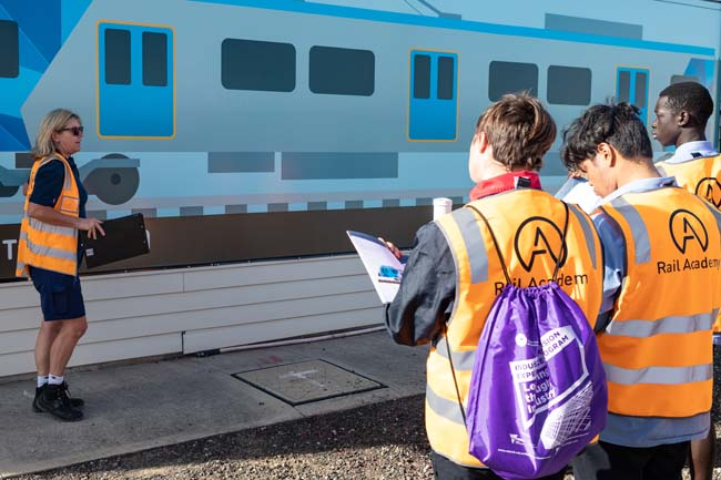 Students standing near a train mural at the Rail Academy Newport for the rail careers event in April